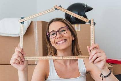 girl smiling and holding house frame during moving