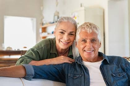 Portrait of happy senior couple relaxing at home and looking at camera. Romantic mature woman embrace from behind her smiling old husband. Cheerful senior couple enjoying life and retirement.