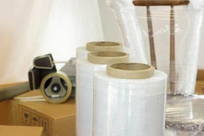 Approach to plastic rolls for packing in the foreground with a plastic wrapped chair, cardboard boxes and adhesive tape in the background