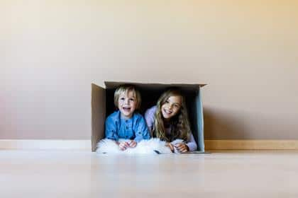Happy brother and sister having fun while being inside of carton box against the wall. Girl is looking at camera. Copy space.