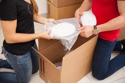 Closeup of a young couple using bubble wrap to pack their stuff in boxes before moving out