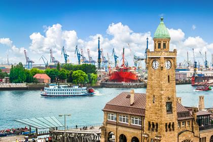 Famous Hamburger Landungsbruecken with harbor and traditional paddle steamer on Elbe river, St. Pauli district, Hamburg, Germany