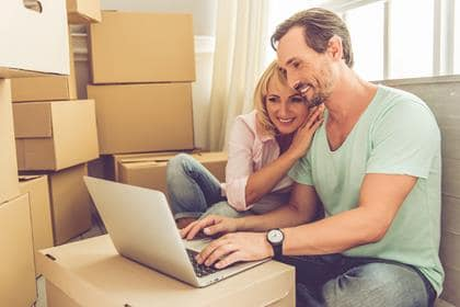 Beautiful mature couple in casual clothes is using a laptop, hugging and smiling while sitting among boxes with their stuff