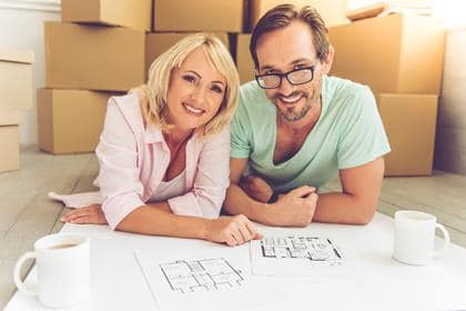Beautiful mature couple in casual clothes is discussing plan of their new house, looking at camera and smiling while lying on the floor near boxes for move
