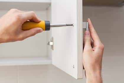 The worker sets a new handle on the white cabinet with a screwdriver