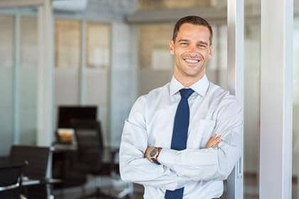 Portrait of cheerful businessman with arms folded standing in conference room. Happy young business man in shirt and tie looking at camera. Portrait of a smiling businessman in modern office with copy space.