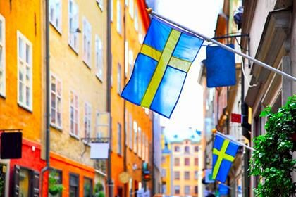 Old street in Stockholm with swedish flags, Sweden. Shallow DOF, focus on the first flag