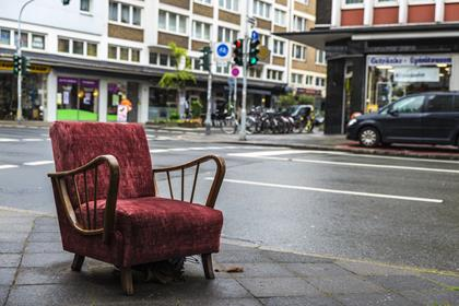 Old armchair vintage garnet lying on the street in Dusseldorf, Germany