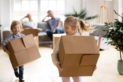 Active children enjoying moving day running carrying boxes, excited kids laughing playing in new home while parents take break to rest, happy girl and boy have fun together, family relocation concept